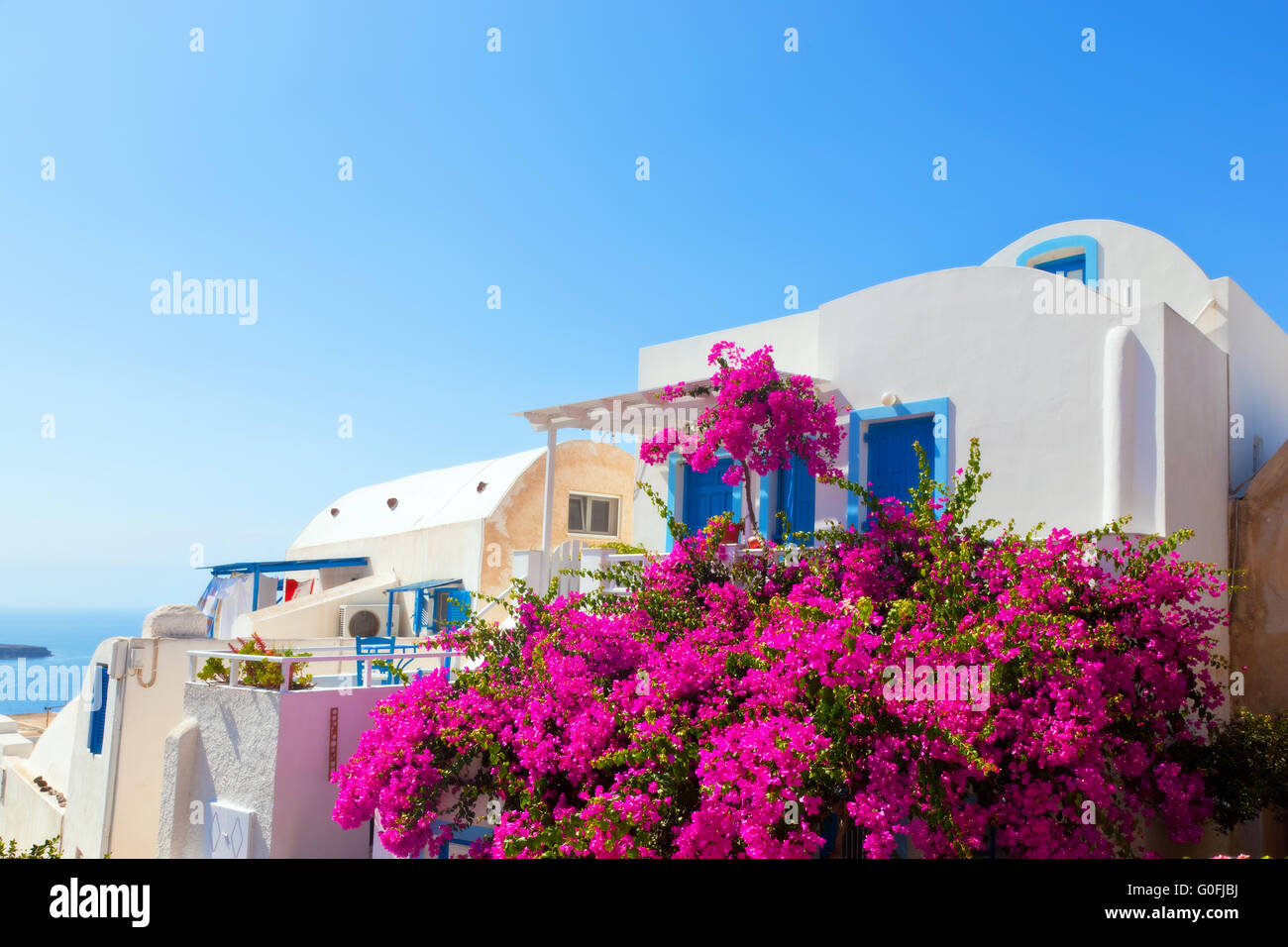 Traditional Greek House traditional greek house with blue door and windows. pink flowers