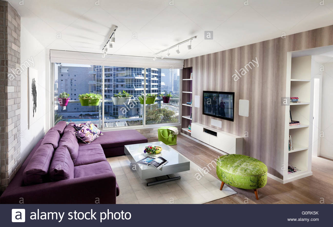Spacious Modern Living Room With Purple Couch And Ceiling To Floor Windows. Exposed  Brick Wall And Striped Wallpaper.