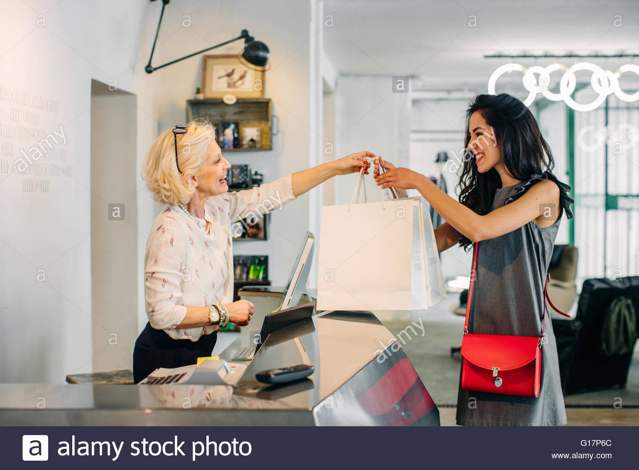Sales assistant handing customer shopping bags Stock Photo ...