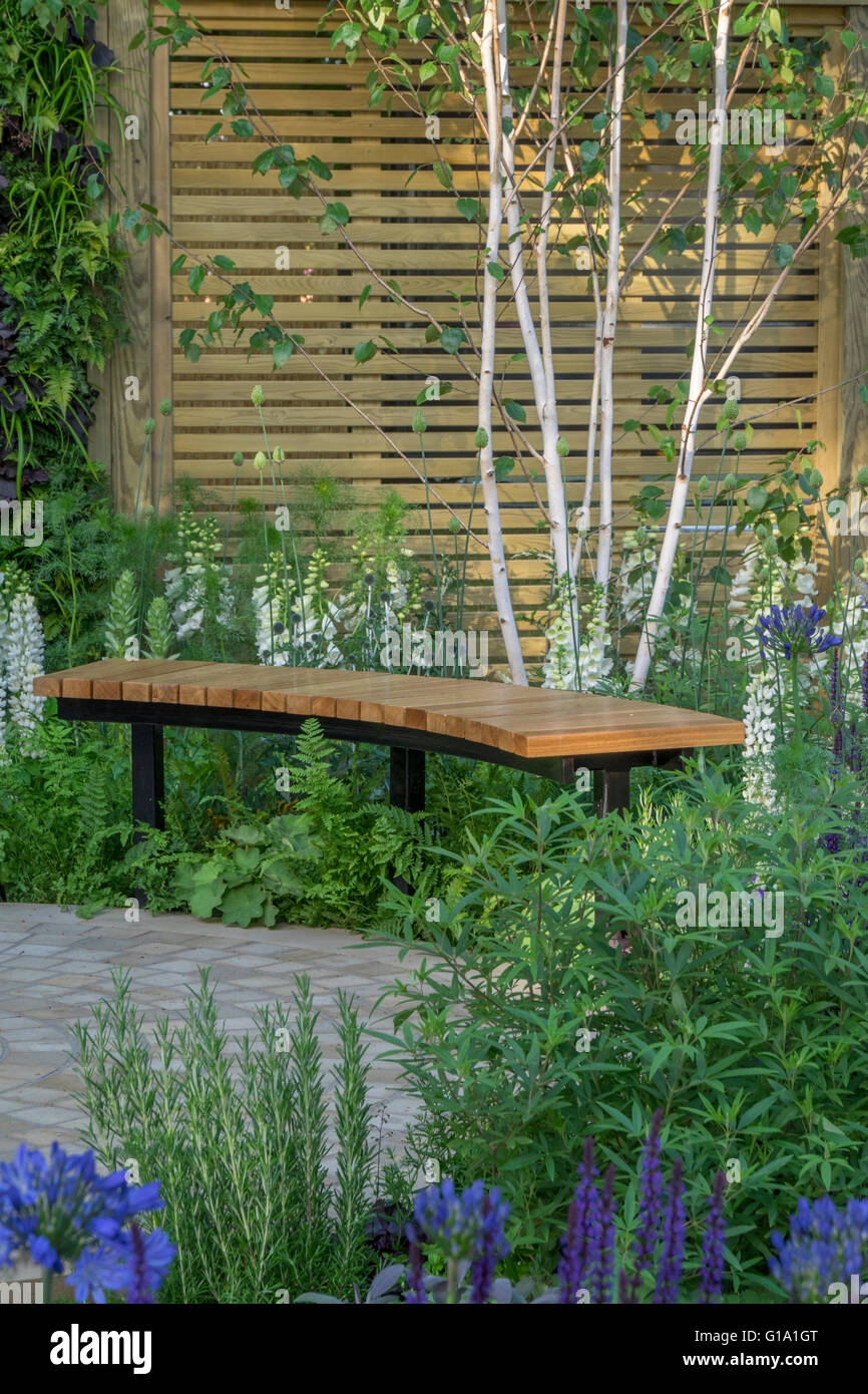 A Curved Garden Bench In A Summer Garden. RHS Hampton Court Show Gardens  2015   The Wellbeing Of Women Garden, Silver Guilt Med