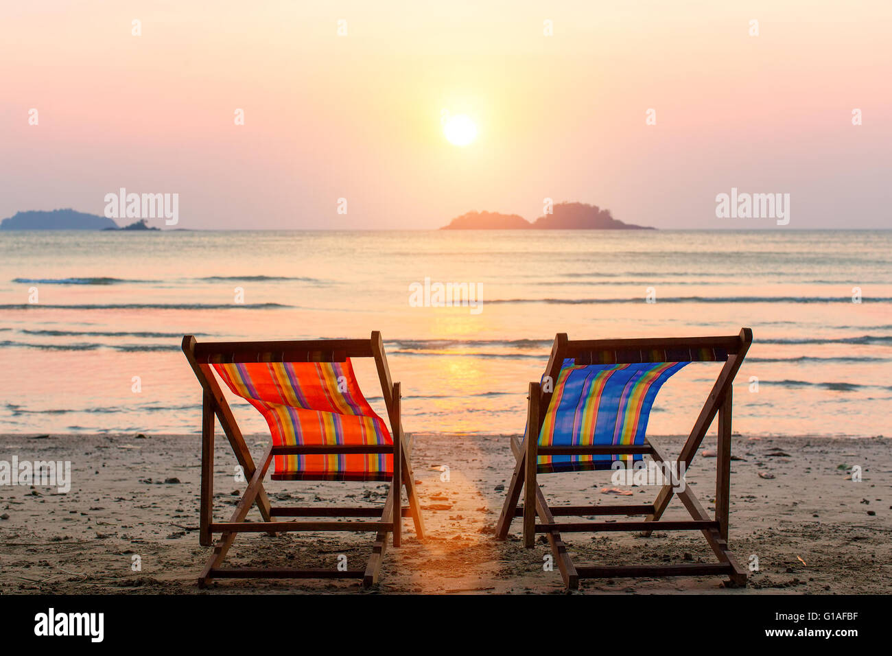 Beach sunset with chairs - Stock Photo Two Lounge Chairs On Sunset Beach