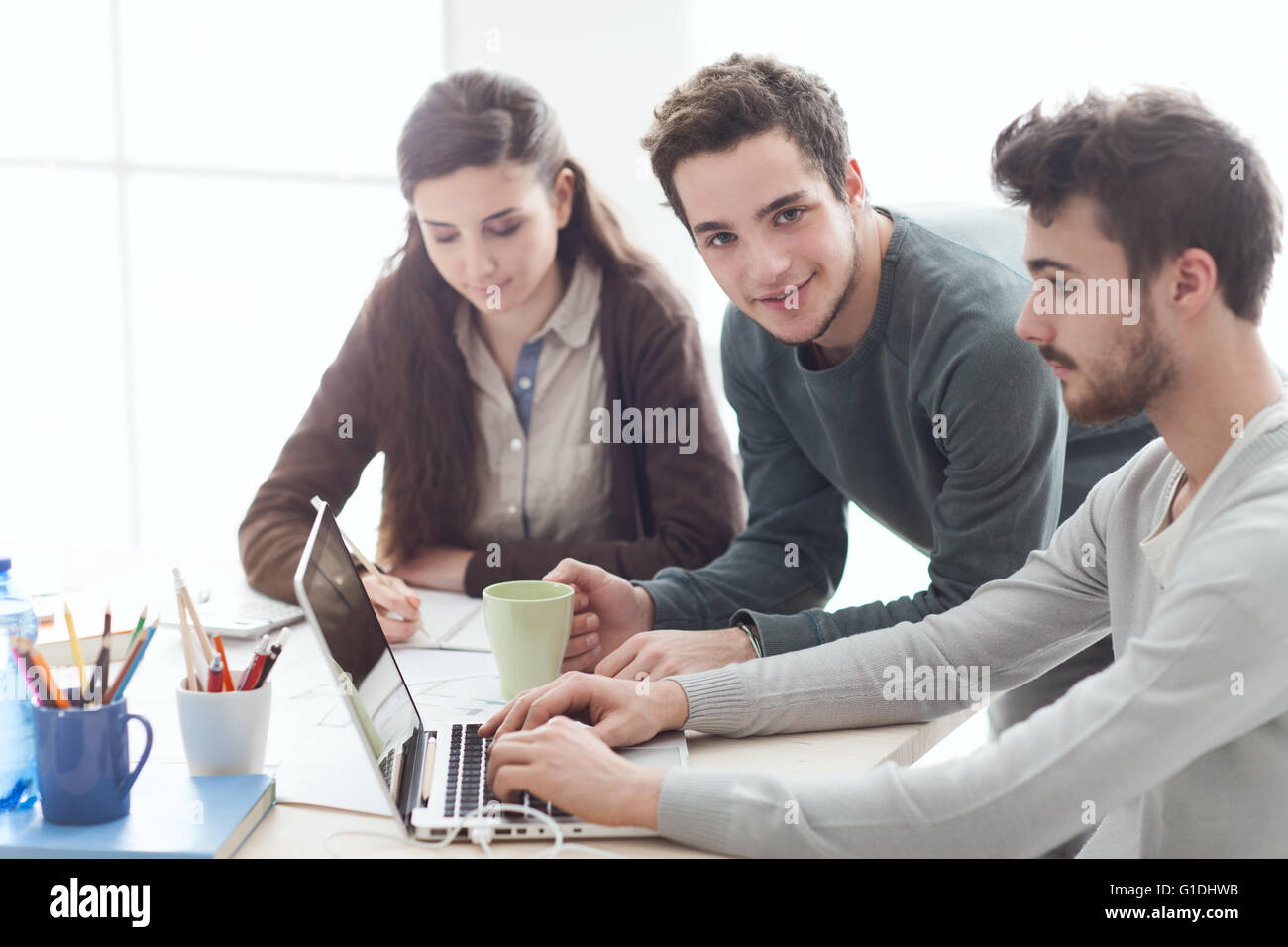 group of college students at desk using a laptop networking and group of college students at desk using a laptop networking and studying together education and learning concept