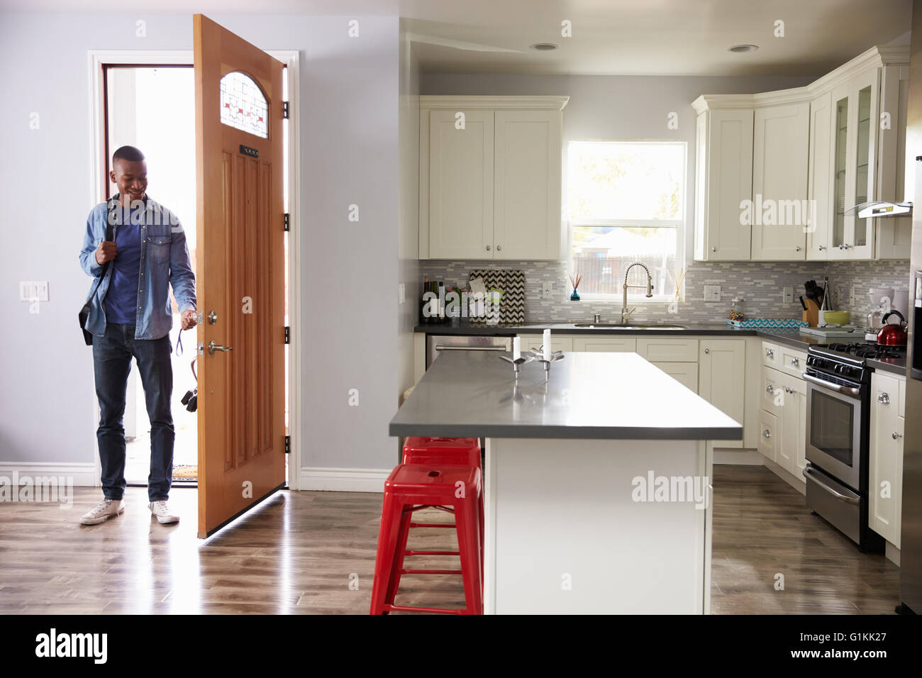 man coming home from work and opening door of apartment stock man coming home from work and opening door of apartment
