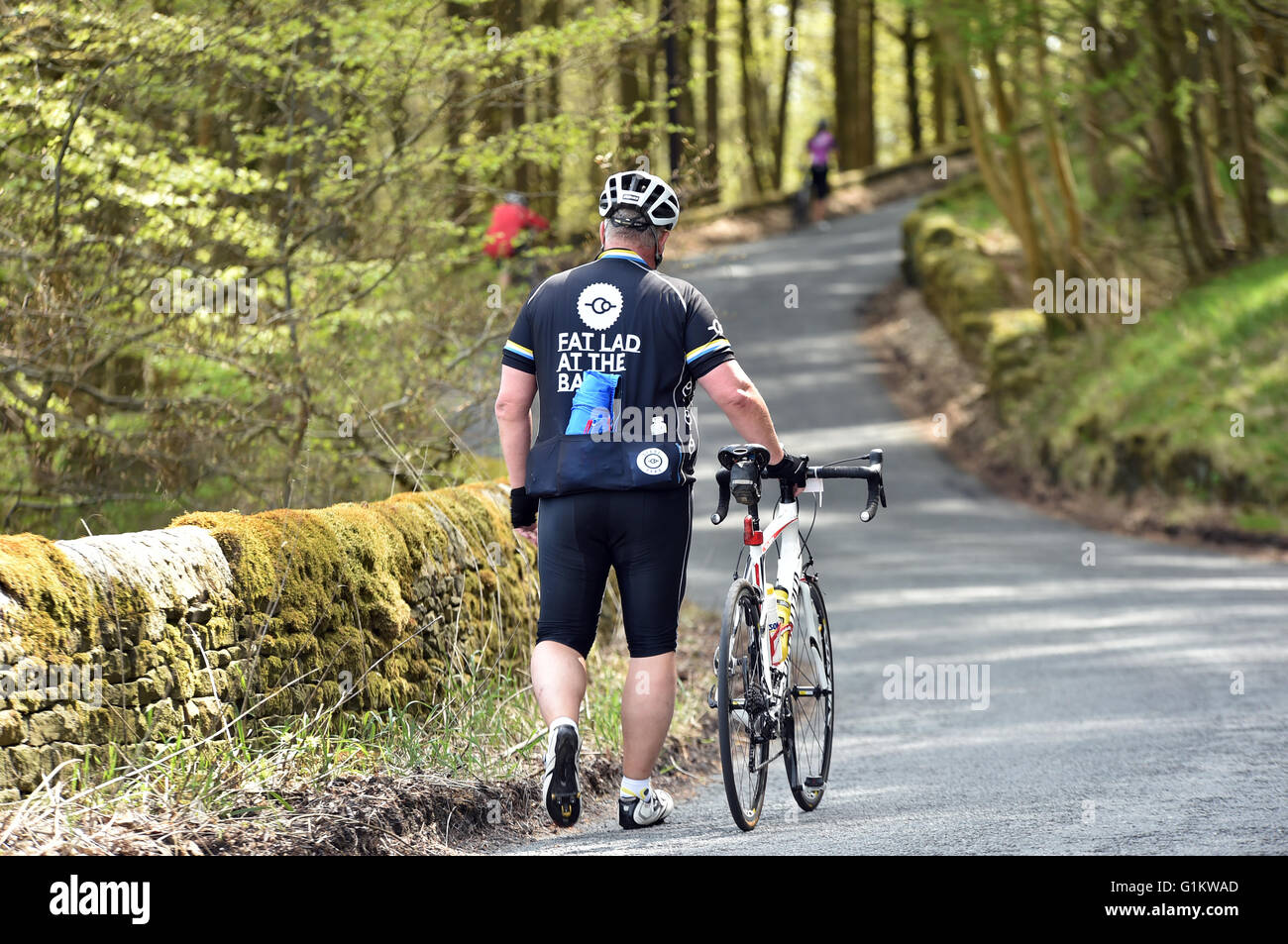 Overweight Cyclist Walking His Bike Up A Hill On A Sportive Stock