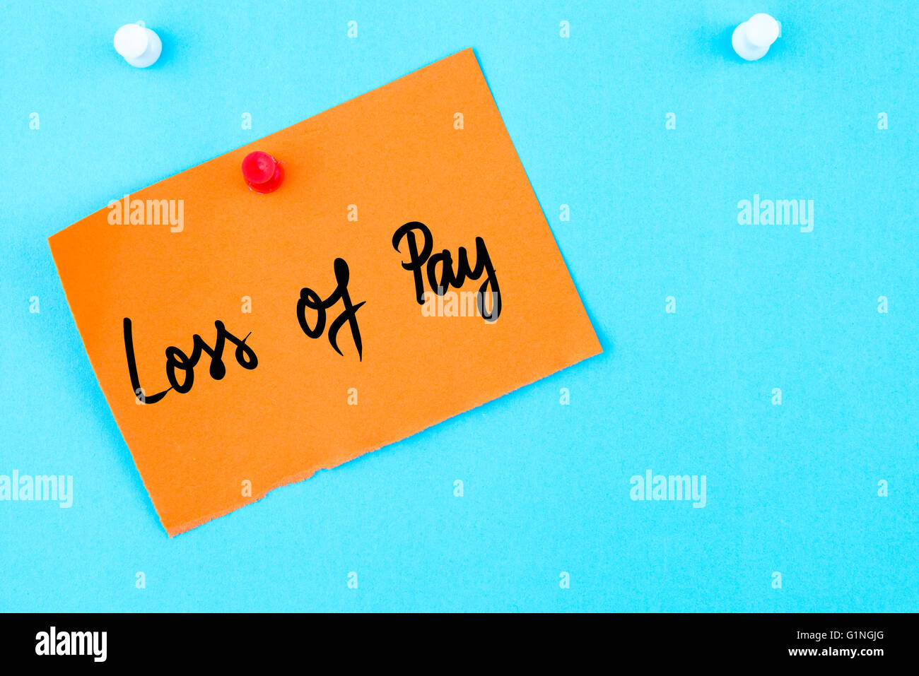 loss of pay written on orange paper note pinned on cork board  loss of pay written on orange paper note pinned on cork board white thumbtack copy space available