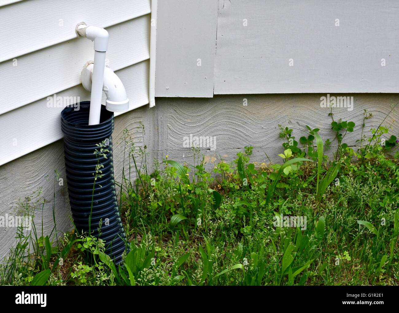 A residential home with a drain pipe on the exterior stock for Water pipe outside house
