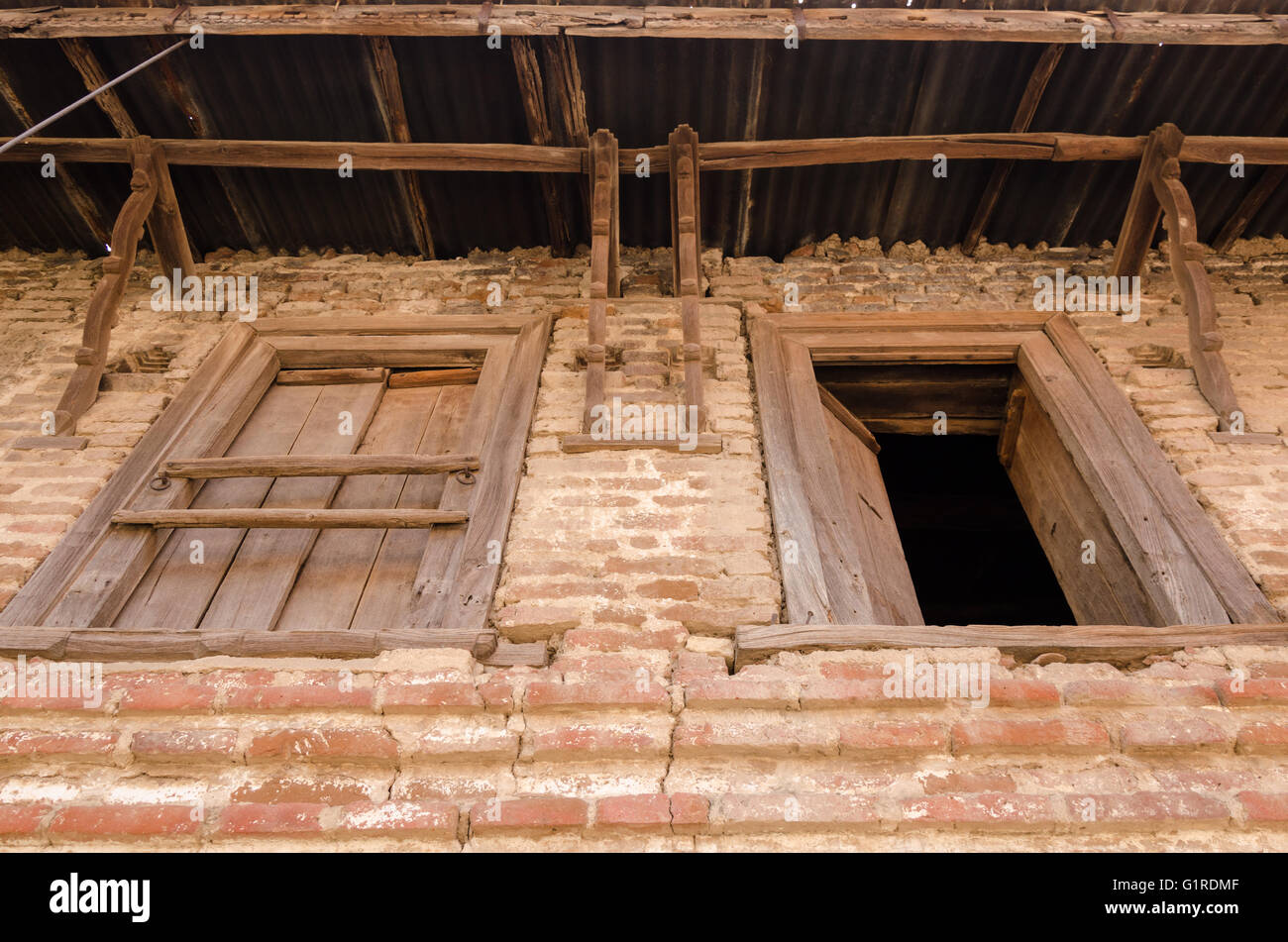 Stock photo wooden windows on stone brick wall of a village house in gujarat india