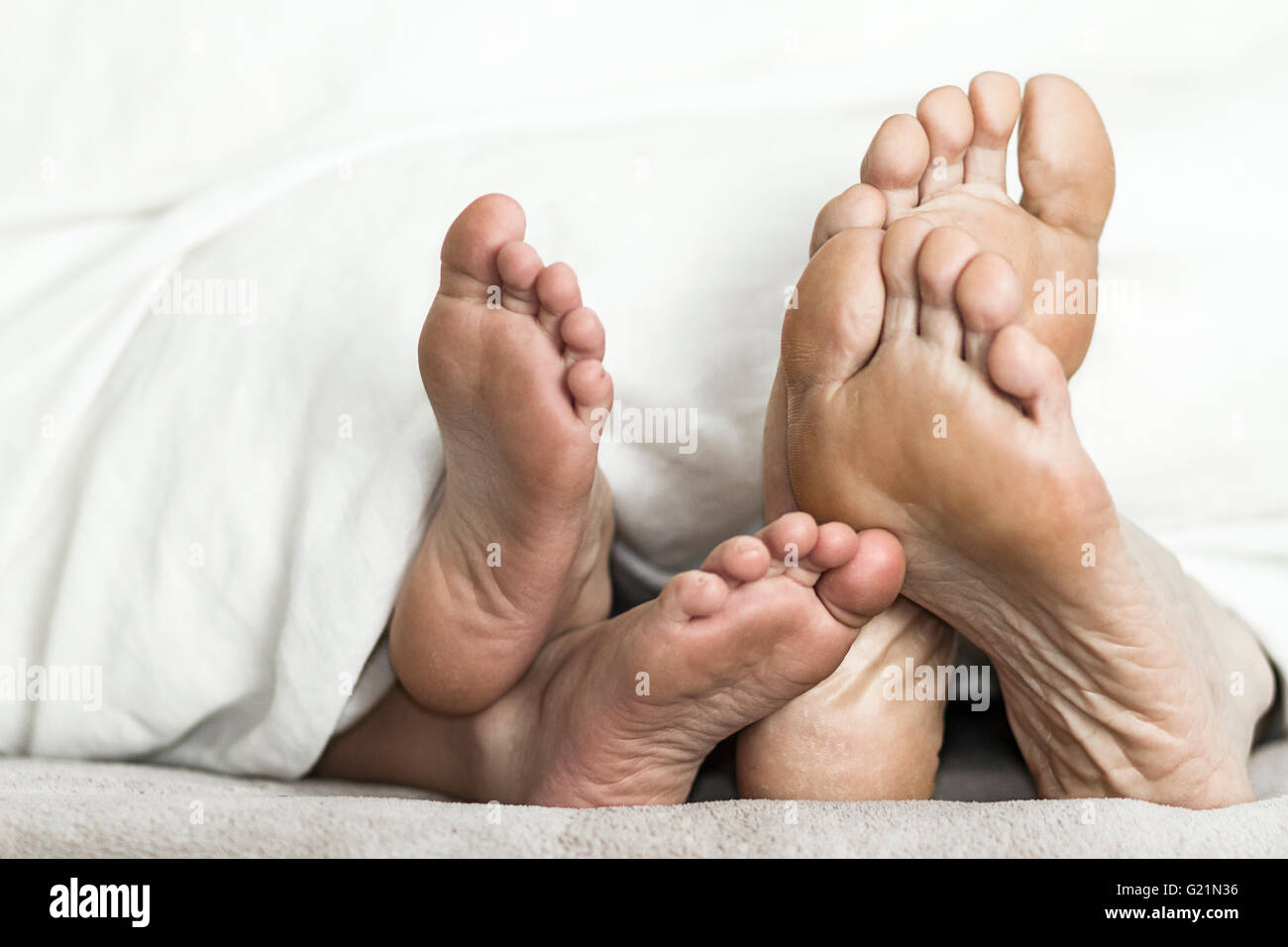 mother and daughter feet in bed stock image
