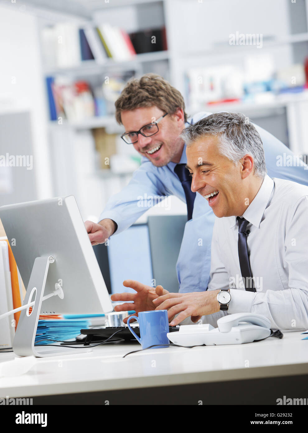 Business People Laughing In Front Of A Screen Computer