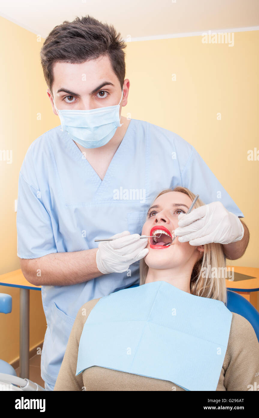 Young Male Dentist At Work With A Beautiful Blonde Female Patient
