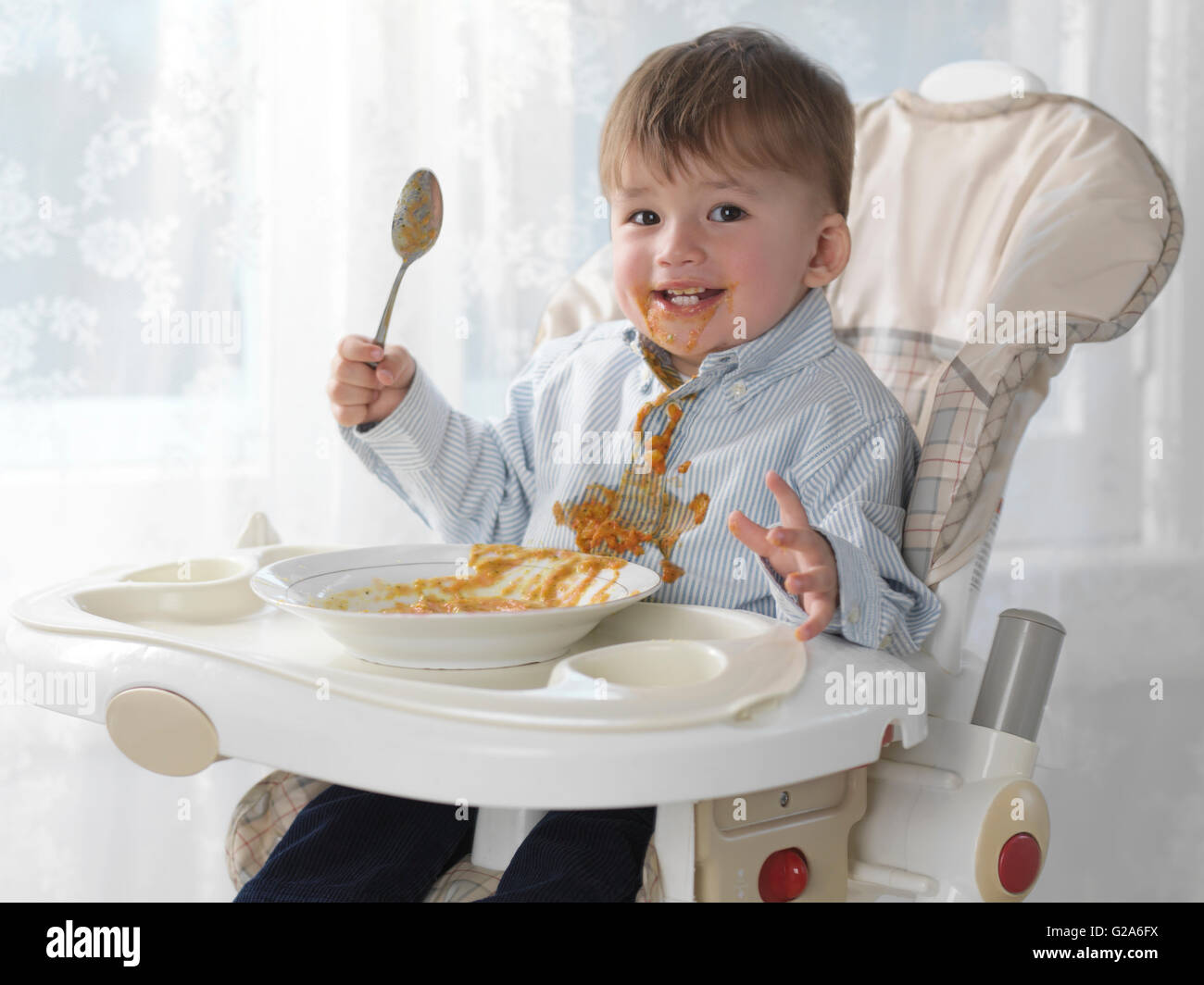 Toddler boy sitting in a high chair eating soup with a for Toddler sitting chair