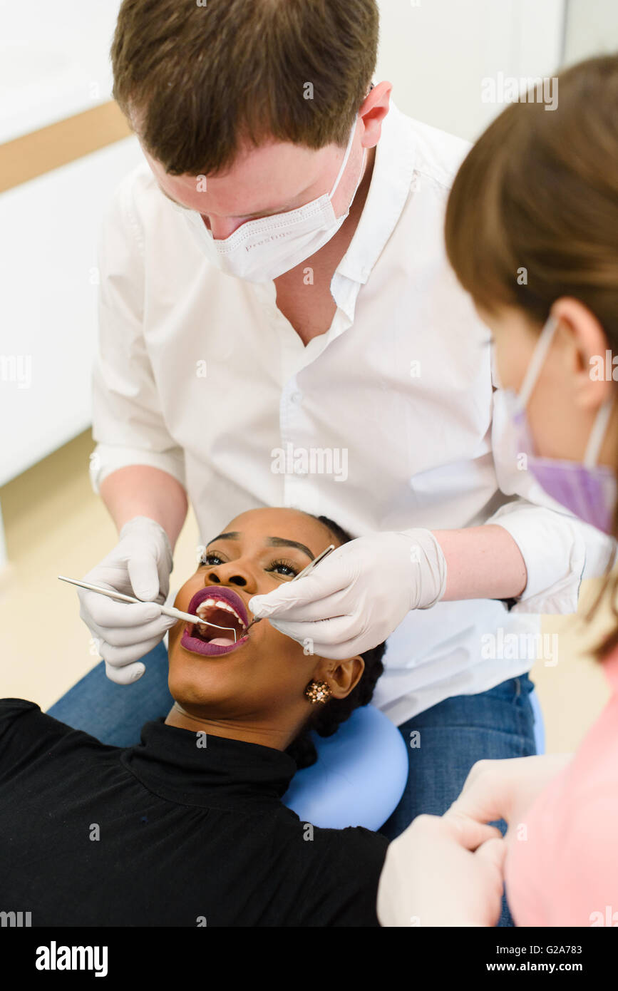 Black American Or African Female Patient With Dentist Assistant In A Dental Treatment Wearing Masks And Gloves