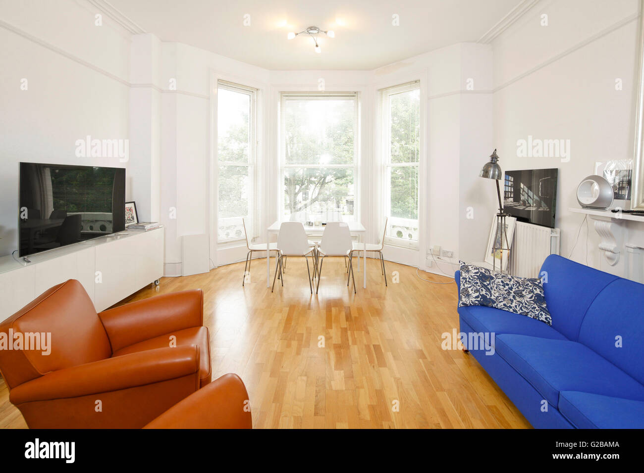 Flat bay windows - Open Plan Living And Dining Room With Bay Windows And Colourful Sofa And Chairs Flat Screen Tv On Side Table Wood Floors With Modern Floor Lamp