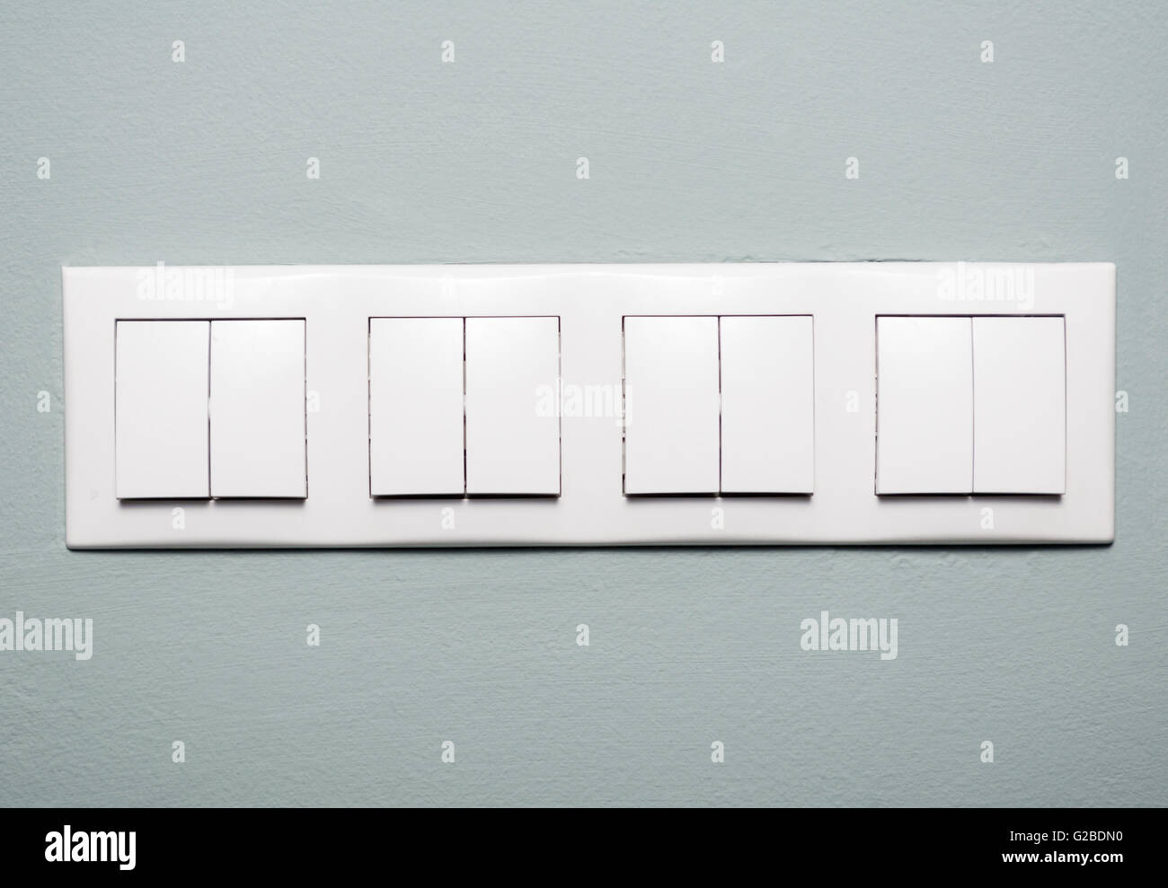 Close-up of multiple light switches on blue background as ...