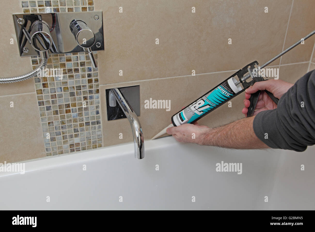 A Workman Uses Mastic Gun To Apply Stone Coloured Silicone Sealant Between Tiles And Bath Edge In Modern Tiled Bathroom