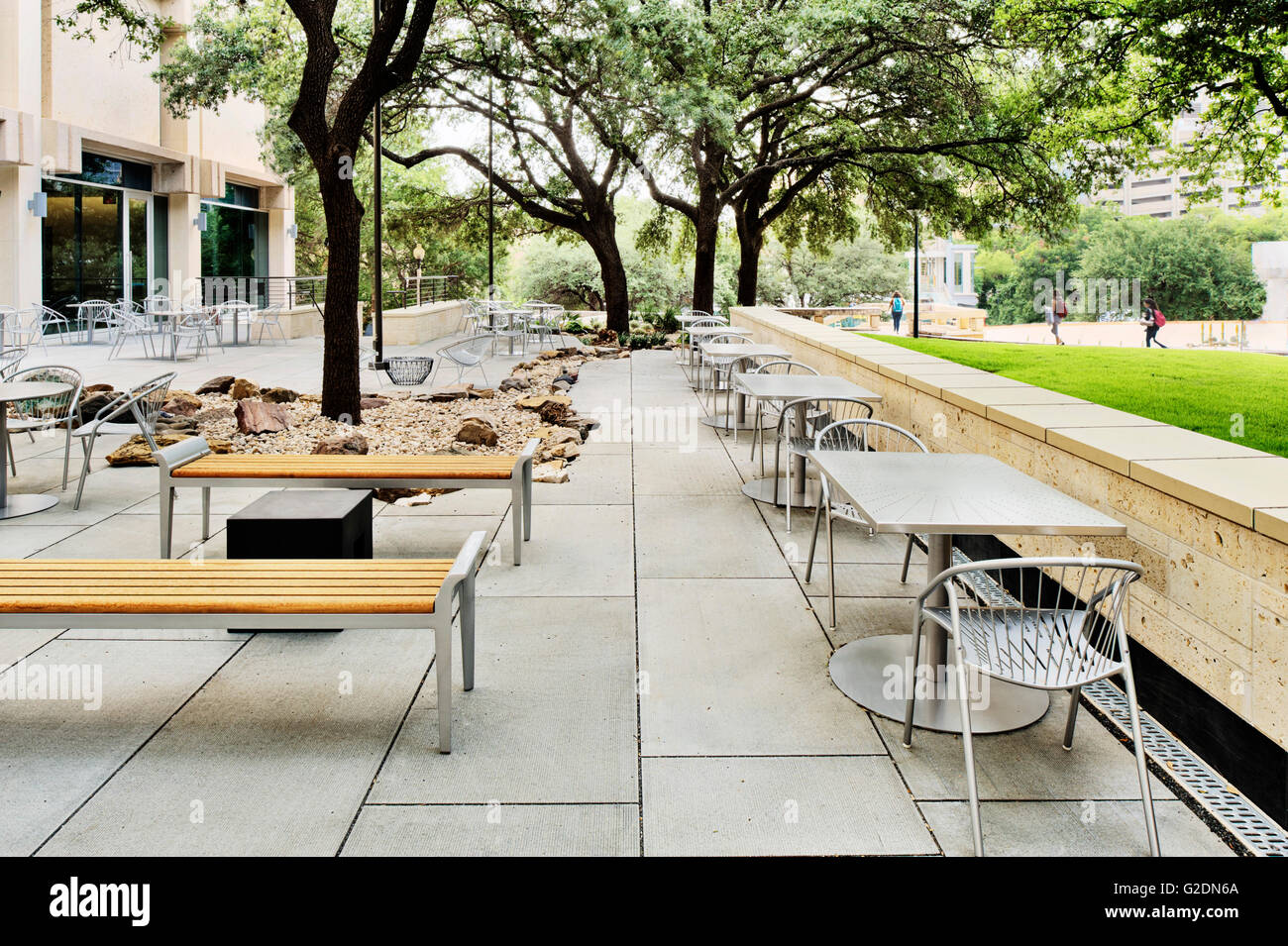 Outdoor Sitting Area Near University Building With Small Tables And Wood  Benches