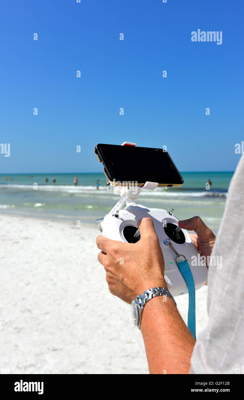 A Mans Hands Holding Radio Controller With Joysticks Piloting An Unseen Non Military Drone Flying Overhead At The Beach