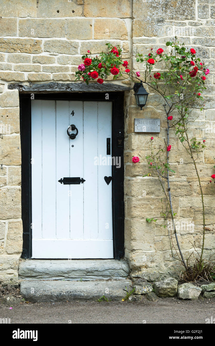Front door of an old english cottage - Cotswold Stone Cottage With Red Roses Around The Front Door Stanton Cotswolds Gloucestershire