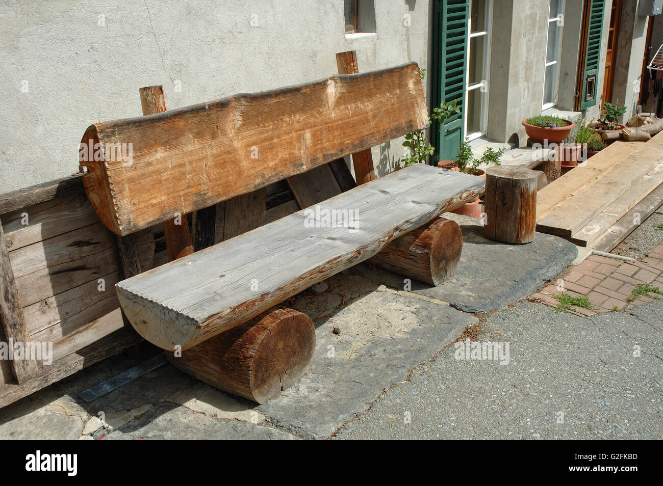 old wooden bench made of tree trunk standing at building wall stock image