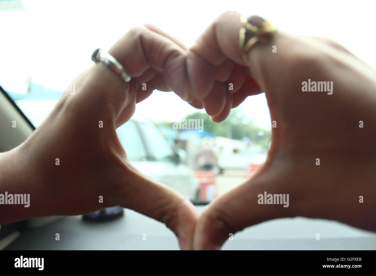 A heart shape sign made by girl hands in the car with bright Stock ...