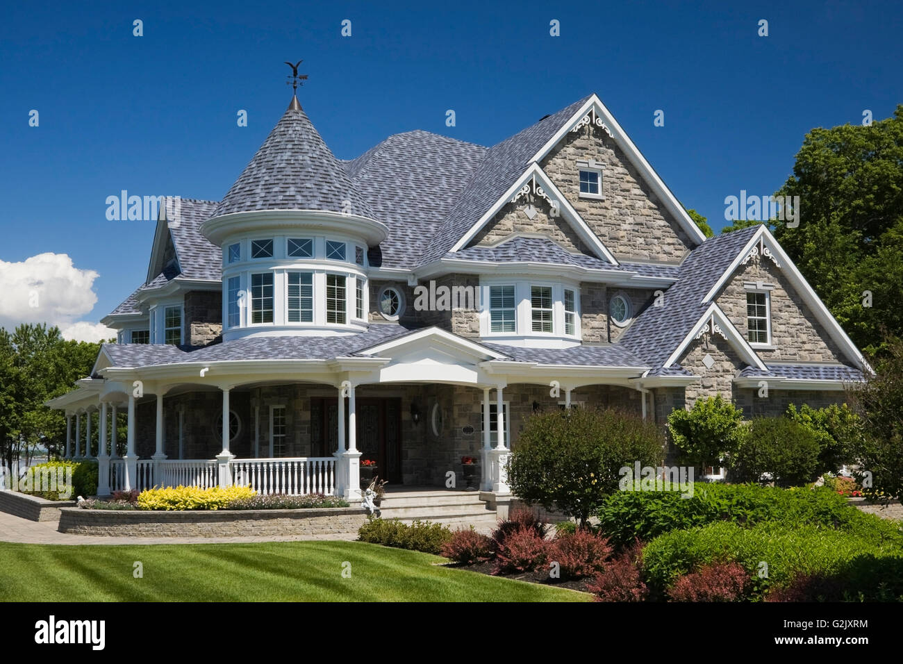 Elegant Grey Stone White Trim Blue Roof Cottage Style Home