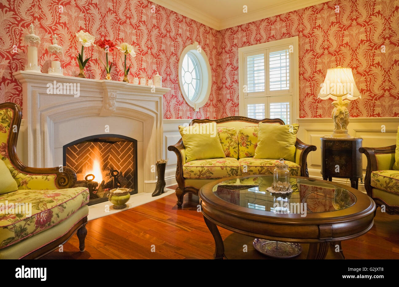 lit gas fireplace yellow flowery upholstered chairs sofa in