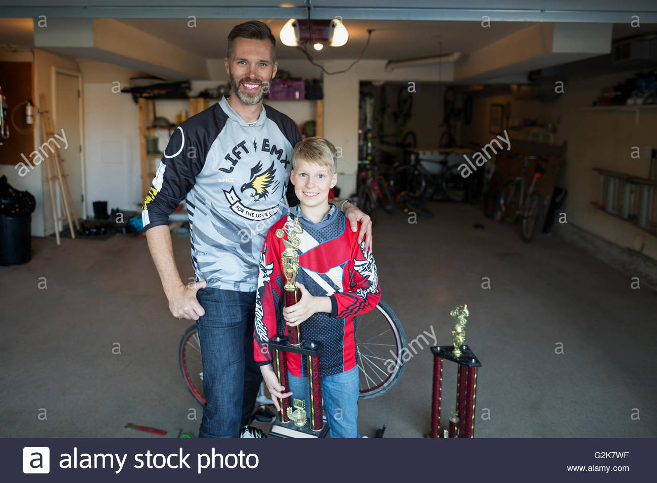 Portrait Smiling Father And Son With Trophies In Garage