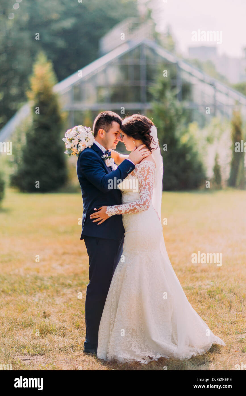 Beautiful Bride With White Wedding Dress And Groom In Stylish Blue Suit Kissing Outdoor On Lawn Greenhouse At Background