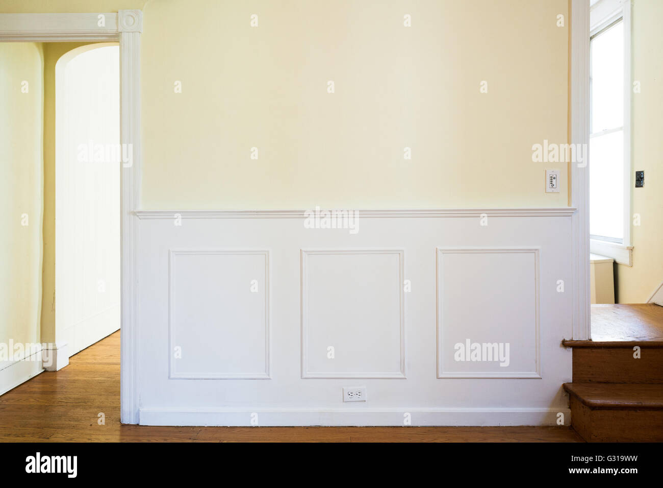 A wall with traditional paneled wainscoting and door molding in an elegant 1920s American townhome dining room & A wall with traditional paneled wainscoting and door molding in an ...