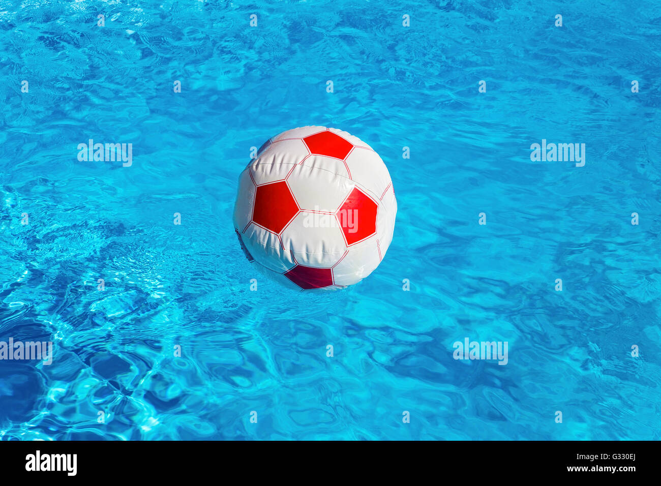 Pool Water With Beach Ball red white beach ball floating on water in blue swimming pool stock