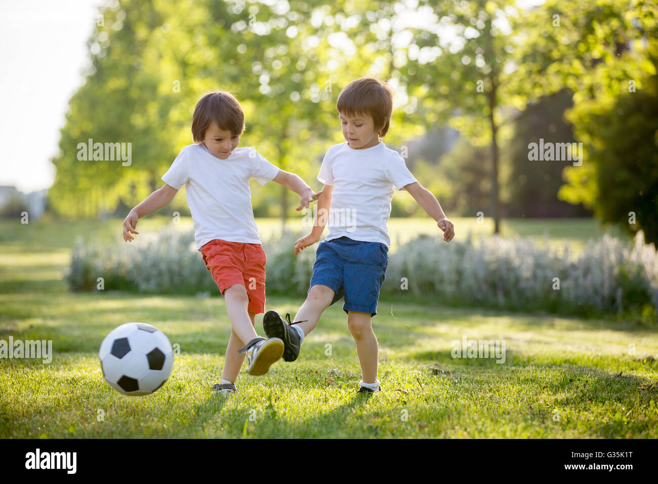 Two cute little kids, playing football together ...