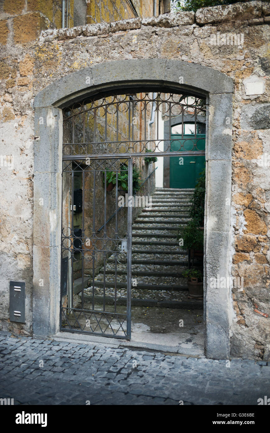 Worn and weathered old stone walls with an open gate leading to steps and a  green door; Orvieto, Umbria, Italy