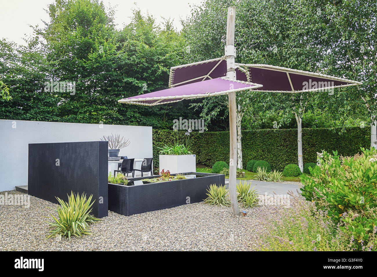 modern garden furniture stock photos  modern garden furniture  - garden with modern garden furniture trendy pond and parasol  stock image