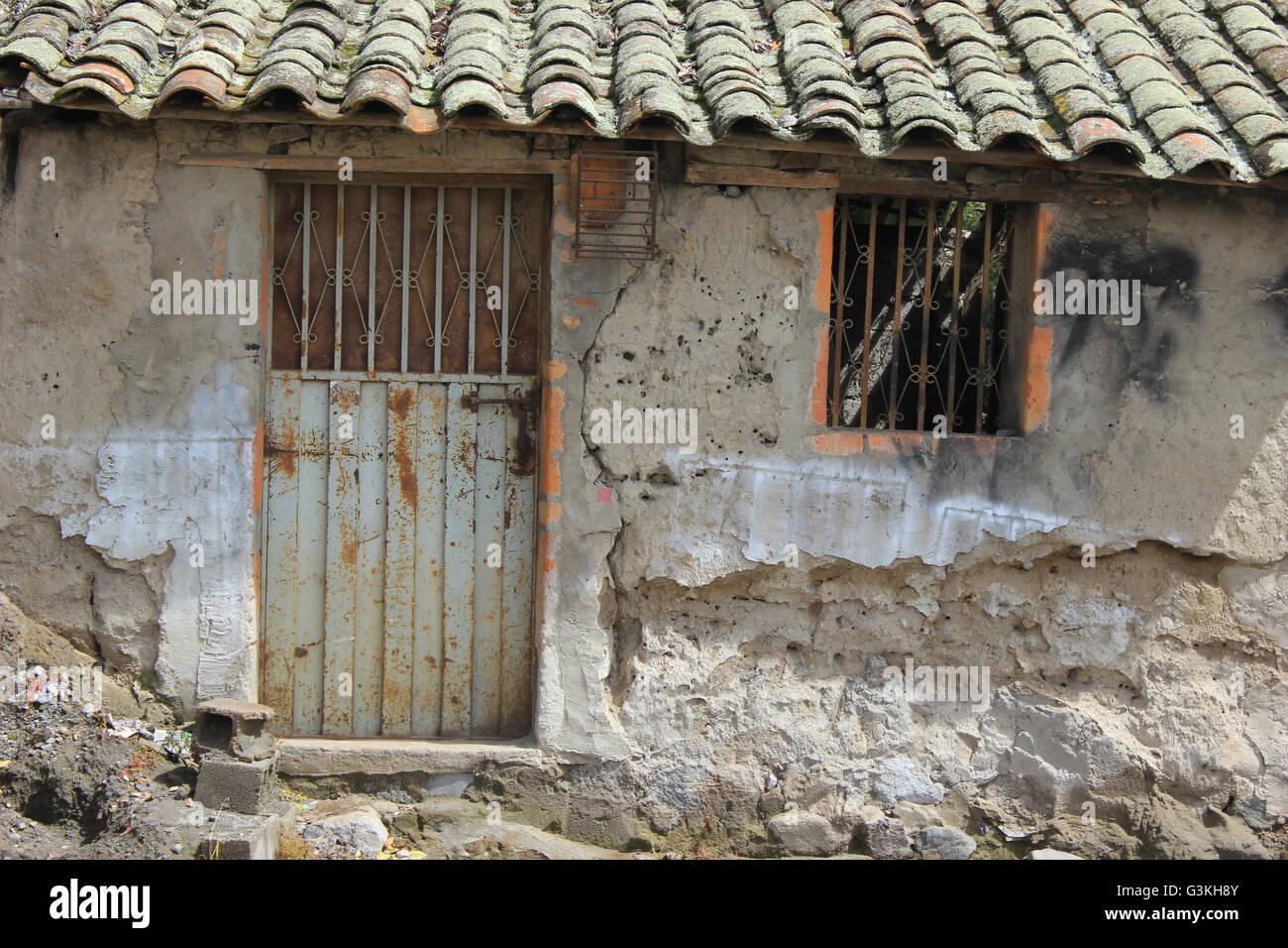 Rusty Metal Door an old building with a rusted metal door and barred window in
