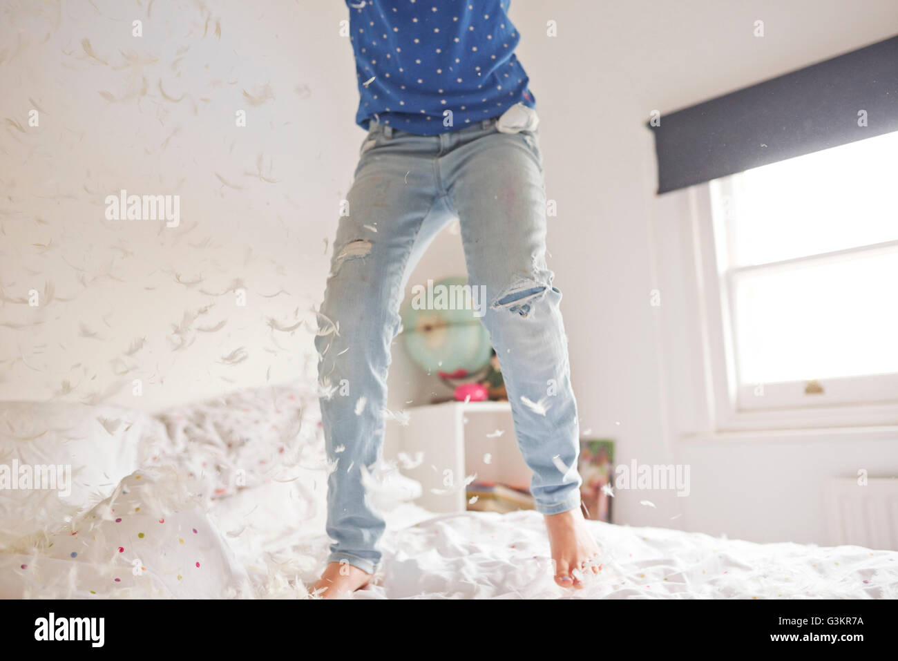stock photo waist down of girl jumping and feather pillow fighting on bed