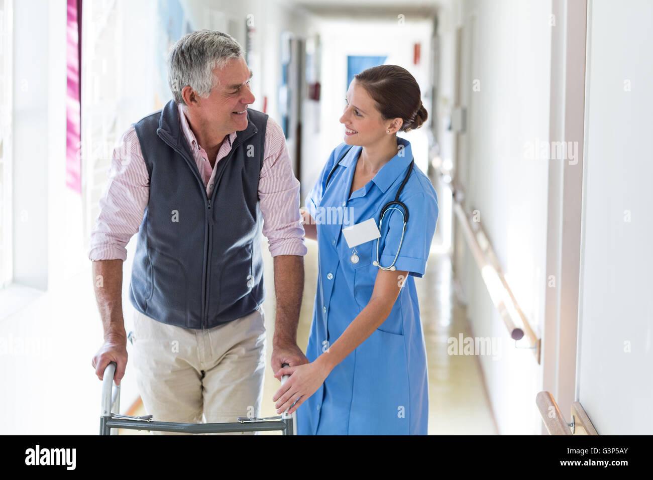 nurse helping senior patient with walking frame stock photo