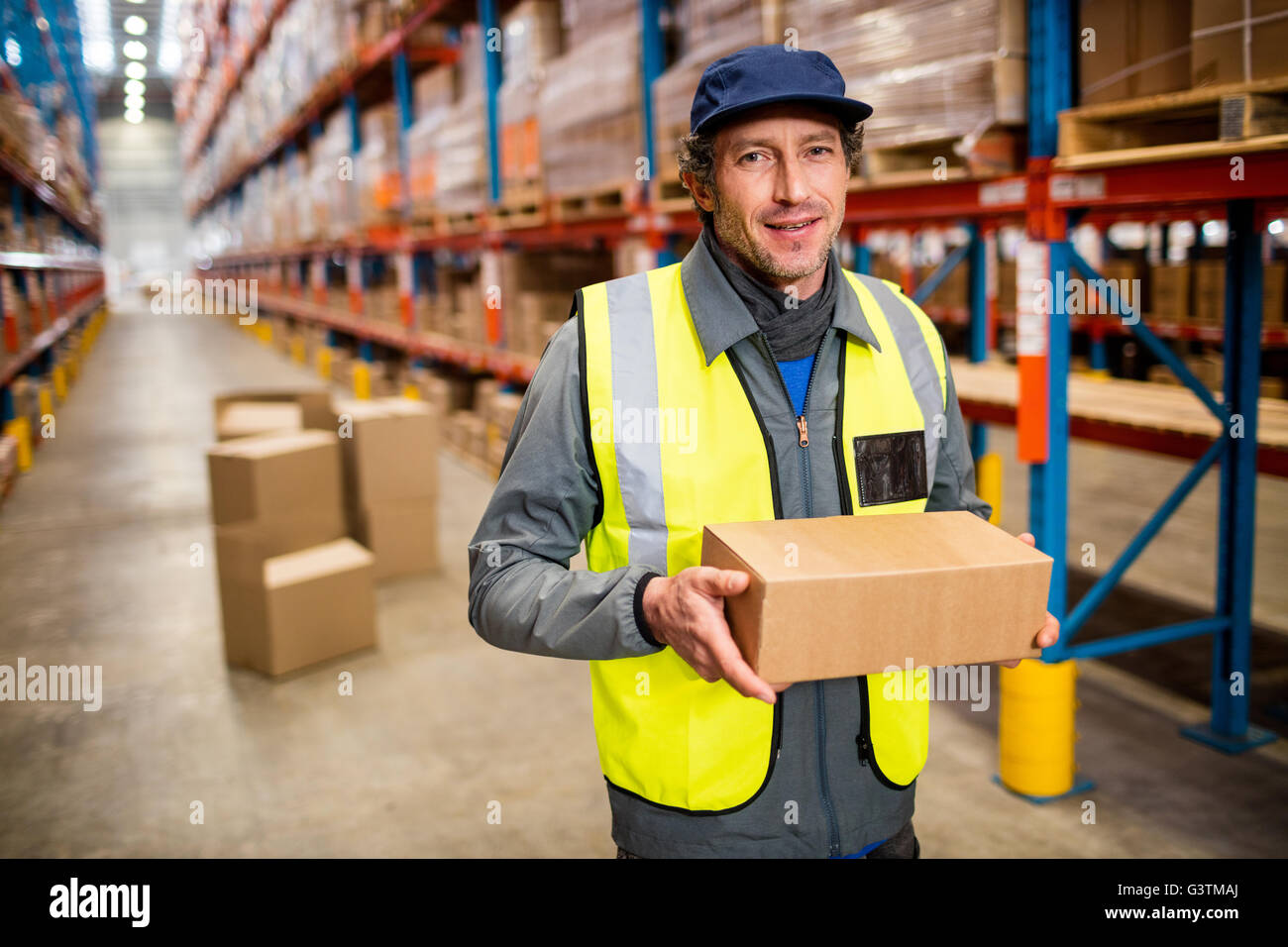 Warehouse worker holding a small box stock photo royalty free stock photo warehouse worker holding a small box sciox Choice Image