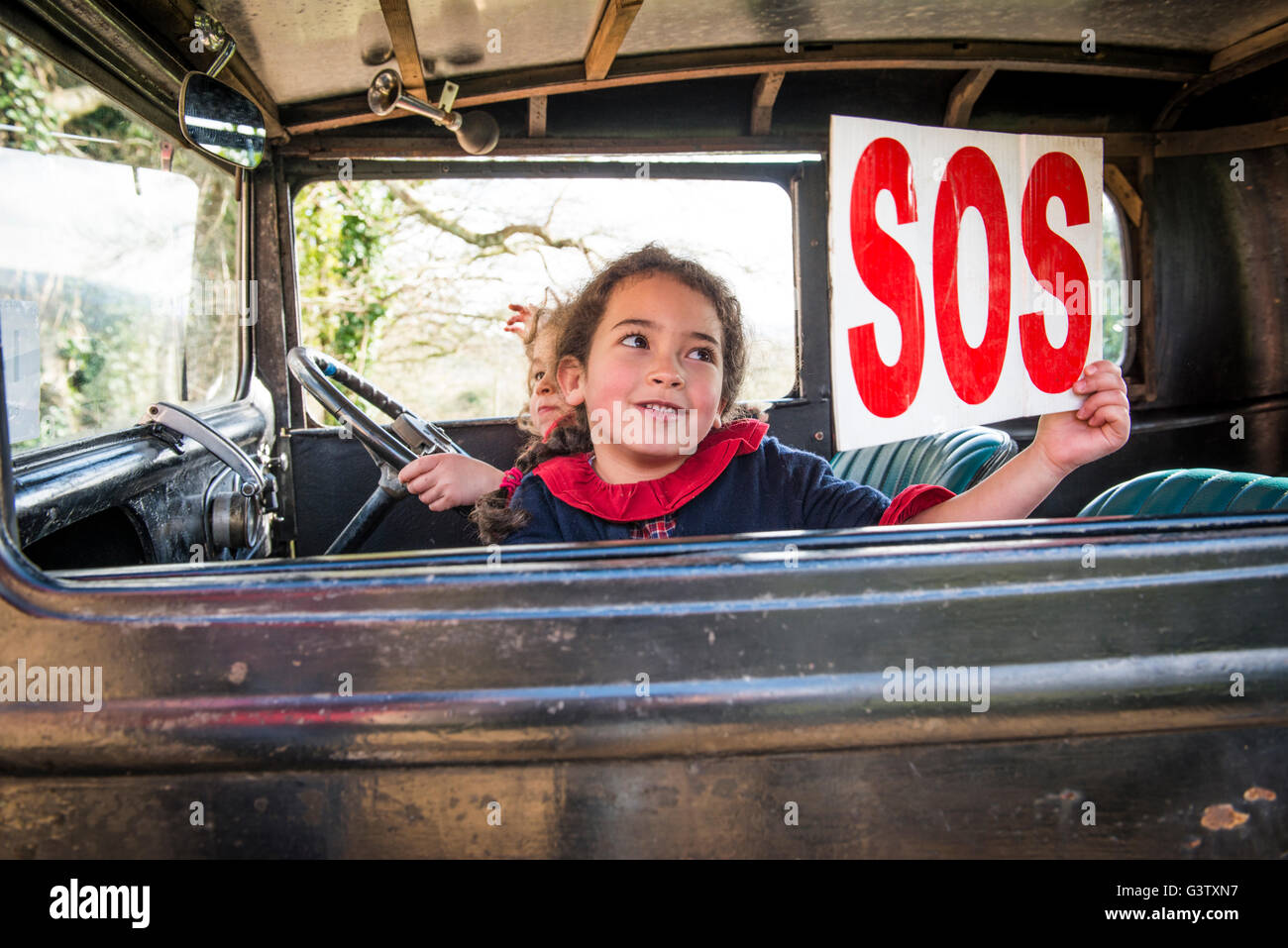a young girl holding an sos sign up in the window of a. Black Bedroom Furniture Sets. Home Design Ideas