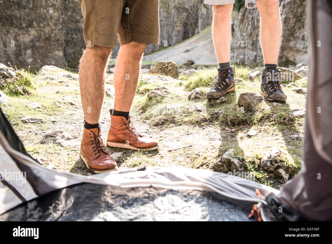 The legs of two men viewed from inside their tent in rugged terrain & The legs of two men viewed from inside their tent in rugged ...