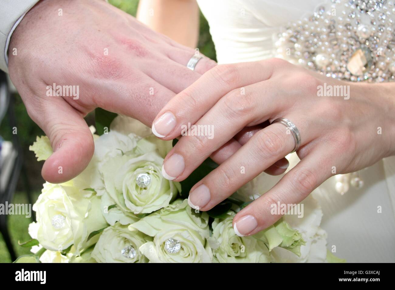 Bride & Groom\'s hands with rings over beautiful flower bouquet ...