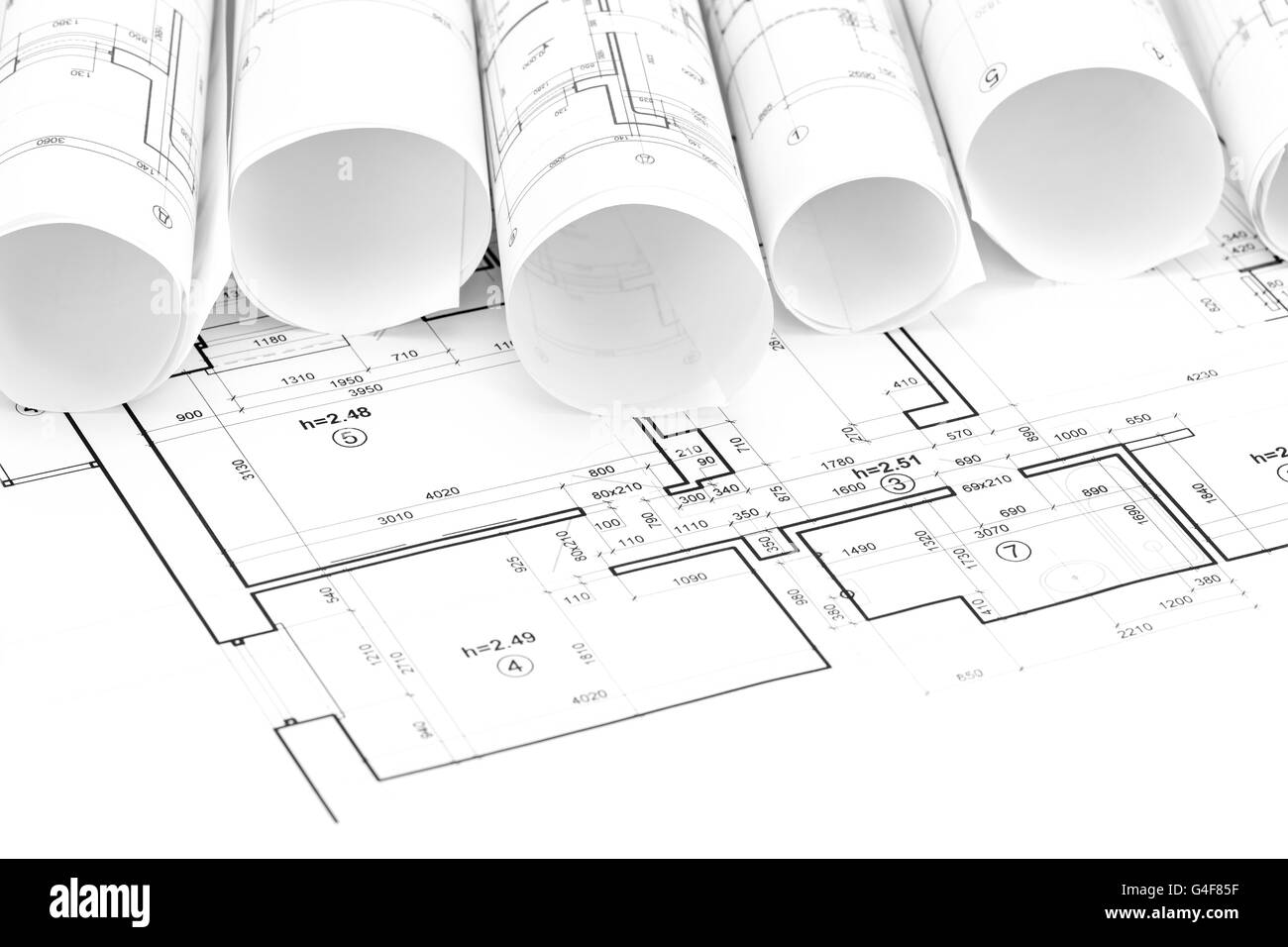 Architectural blueprint rolls and floor plans on desk stock photo architectural blueprint rolls and floor plans on desk malvernweather Image collections