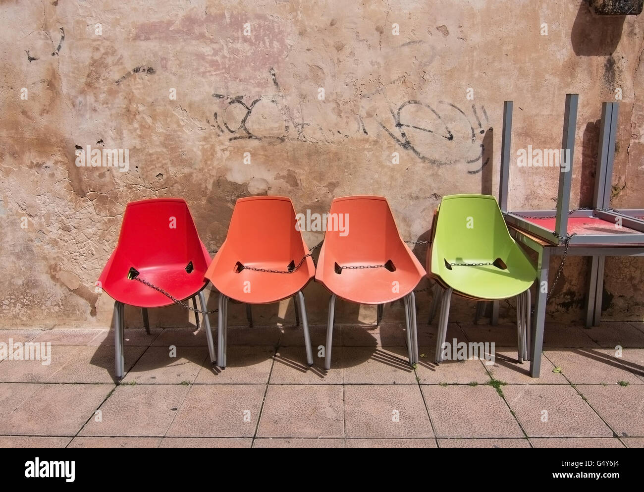 Four Colorful Plastic Chairs In Color Order Chained Together Against Stone  Wall With Washed Graffiti In