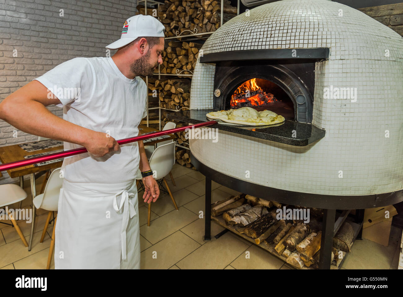 Mediterranean wood fired pizza oven - Young Kitchen Chef Check Pizza In Traditional Wood Fired Oven Stock Image