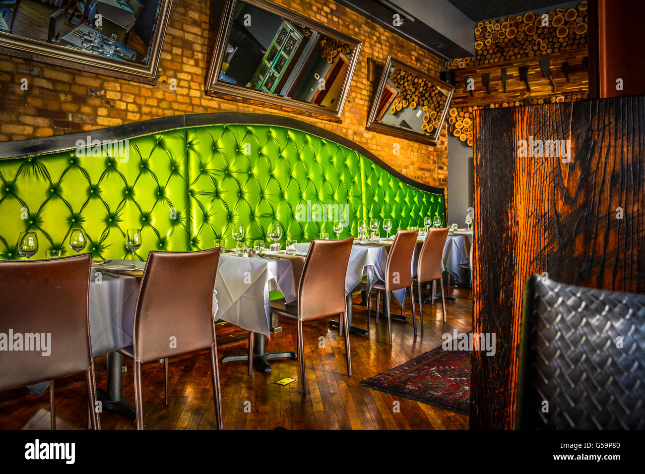 the posh lime green upholstered booths with brick-lined walls in