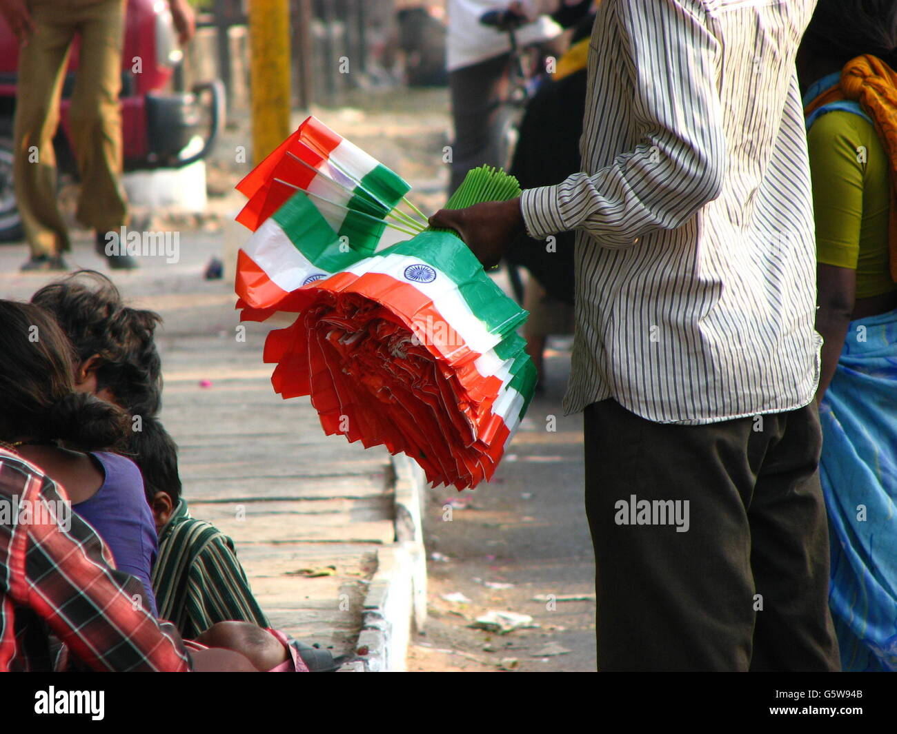 poor people in india selling flags on the eve of indian