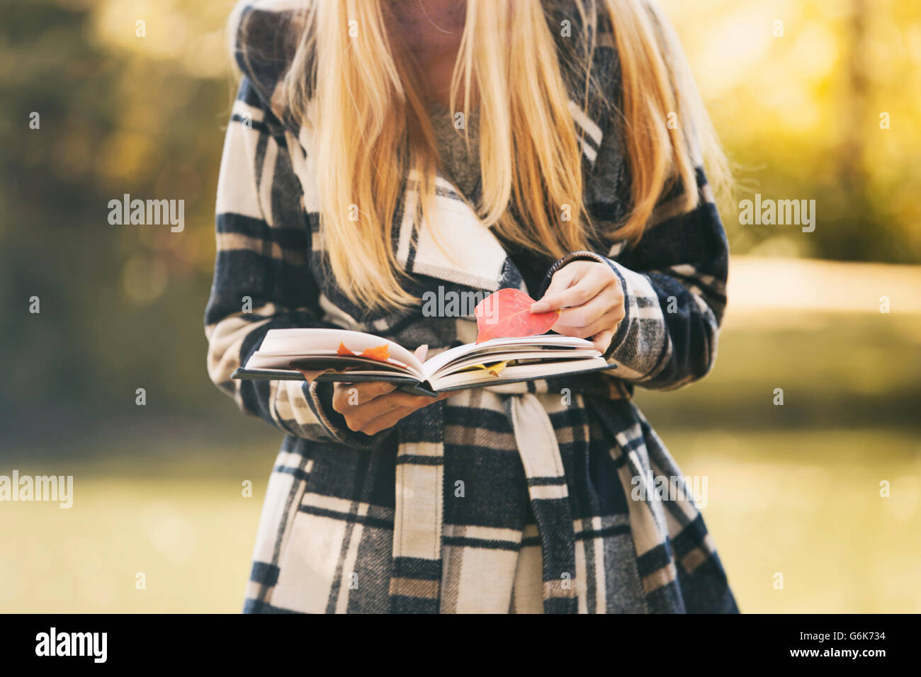 From the book where you might see the beautiful autumn leaves - Stock Photo Teenage Girl Holding Book And Autumn Leaves