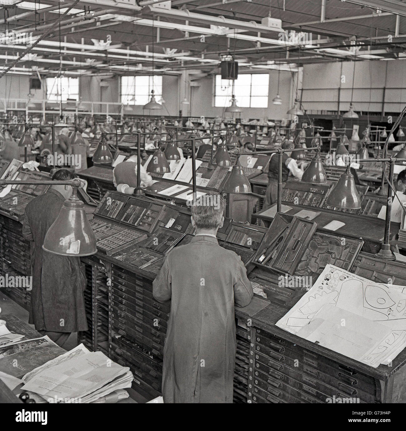 1950s historical picture of the large typsetting department of the process of manual typesetting pages of books using stored letters and symbols to buycottarizona