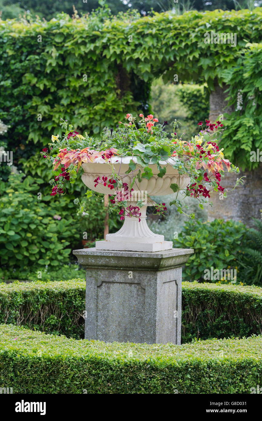 Stone Urn Full Of Flowers In A Cotswold Garden. Cotswolds