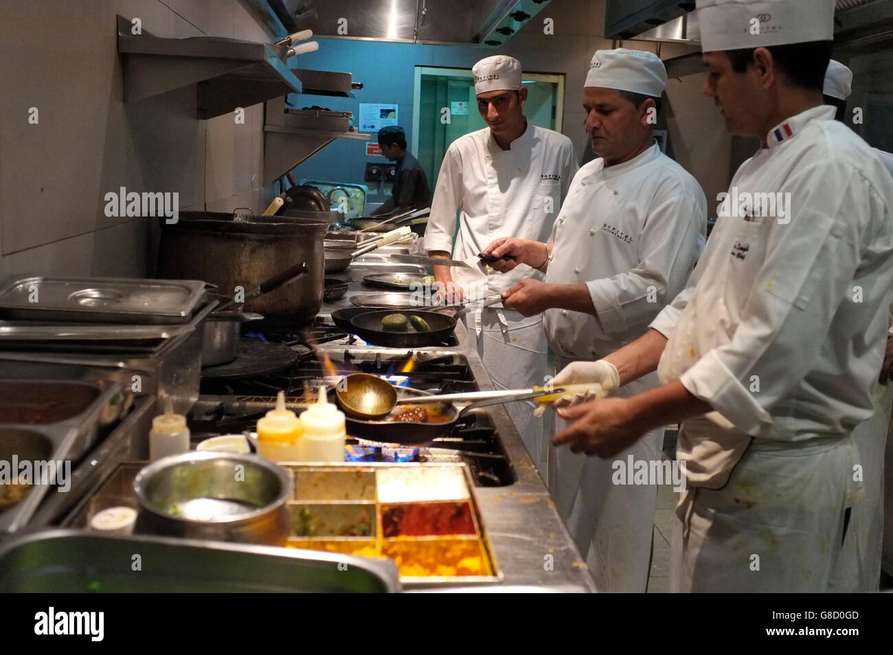 Chefs prepare food at the kitchen in jyran restaurant for Kitchen 8 restaurant