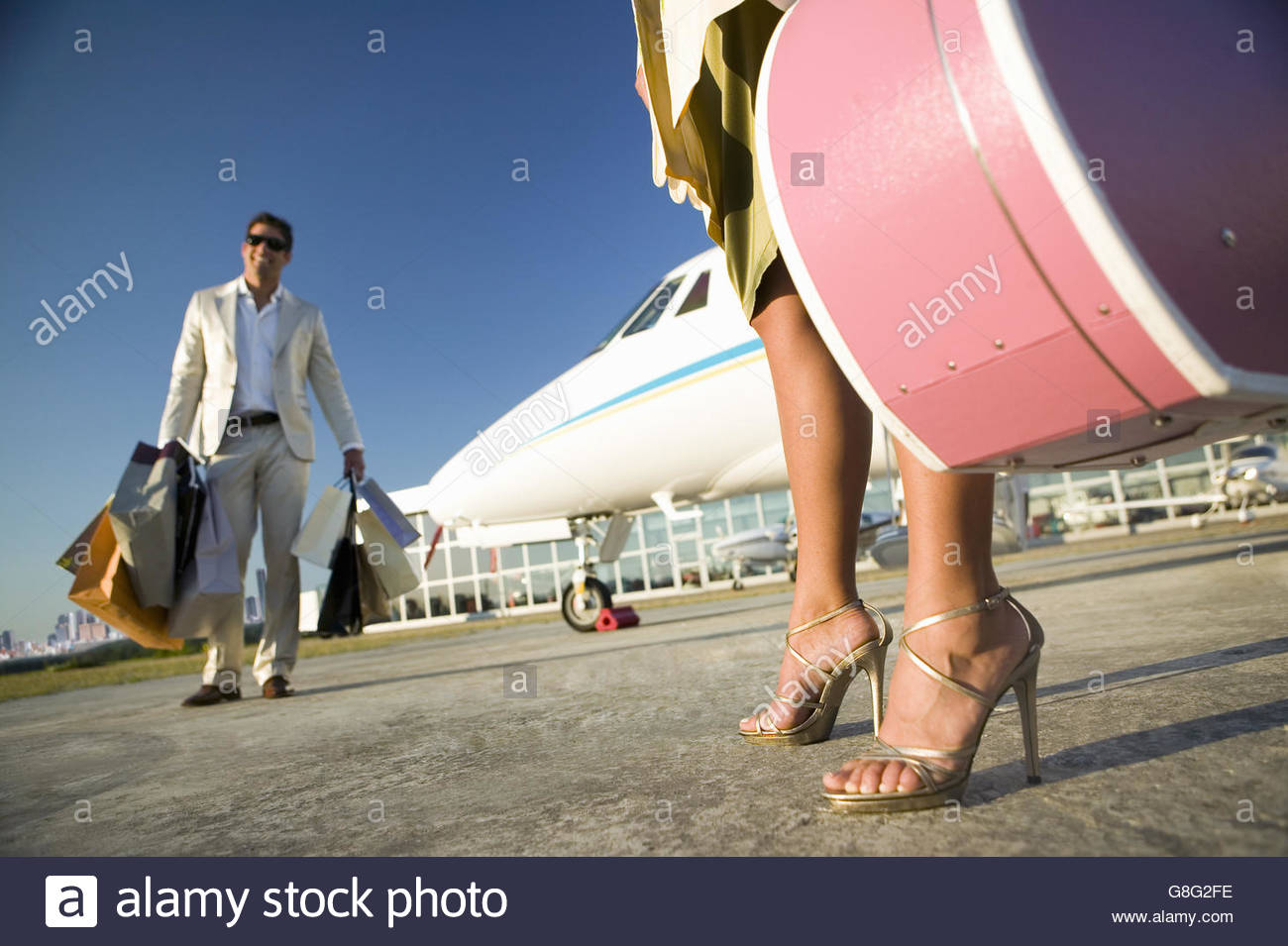 Couple with suitcases and shopping bags next to airplane Stock ...